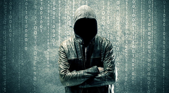 evil hacker in a hoodie in front of computer code